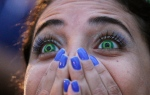 In this July 8, 2014 file photo, a Brazil soccer fan wearing contact lenses that mimic the Brazilian flag reacts as she watches her team play Germany in a World Cup semifinal game via live telecast inside the FIFA Fan Fest area on Copacabana beach in Rio de Janeiro, Brazil. (Leo Correa)