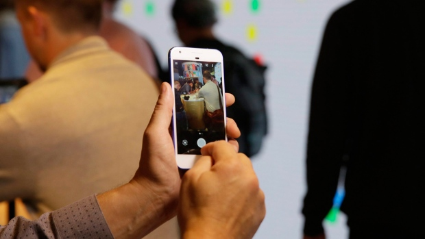 A reporter looks over the new Google Pixel phone in San Francisco, on Oct. 4, 2016. (Eric Risberg / AP)