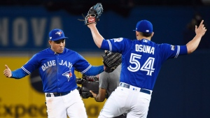Toronto Blue Jays right fielder Ezequiel Carrera (3) and relief pitcher Roberto Osuna (54) celebrate their victory over the Cleveland Indians in game four American League Championship Series baseball action in Toronto on Tuesday, October 18, 2016. (THE CANADIAN PRESS / Nathan Denette)