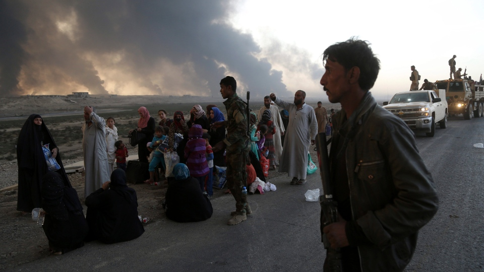 Smoke rises as people flee their homes during clashes between Iraqi security forces and members of the Islamic State group fleeing Mosul, Iraq, Tuesday, Oct. 18, 2016.  (AP Photo)