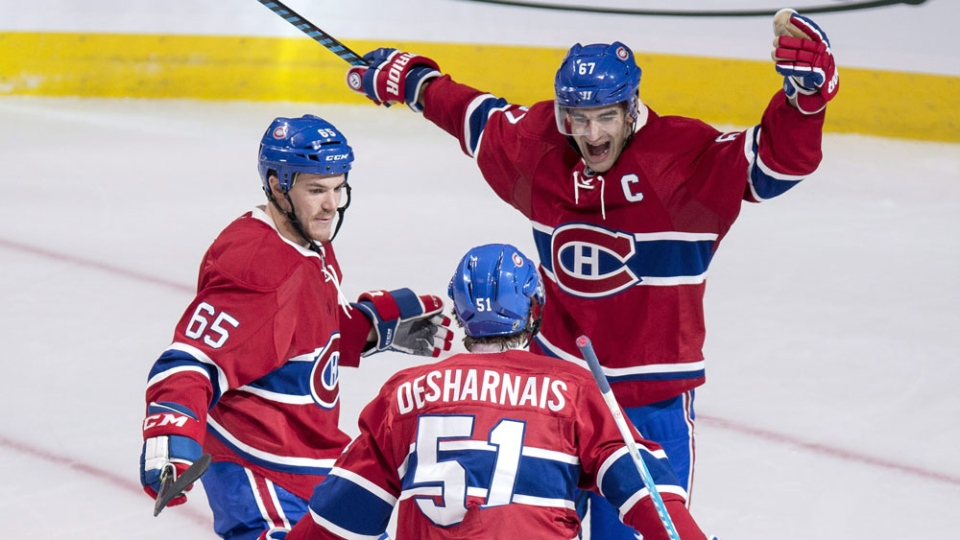 Montreal Canadiens' David Desharnais celebrates his goal against the Pittsburgh Penguins with teammates Max Pacioretty, right, and Andrew Shaw during second period NHL hockey action Tuesday, October 18, 2016 in Montreal. THE CANADIAN PRESS/Paul Chiasson