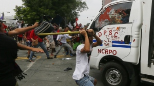 Protesters hit a Philippine National Police van after it rammed into protesters outside the U.S. Embassy in Manila Wednesday, Oct. 19, 2016. (AP / Bullit Marquez)