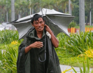 A man walks along a boulevard with an inverted umbrella under a slight rain which was brought about by Typhoon Karika Sunday, Oct. 16, 2016 in Manila, Philippines.  (AP Photo/Bullit Marquez)