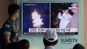 A South Korean army soldier watches a TV news program showing images published in North Korea's Rodong Sinmun newspaper of North Korea's ballistic missile believed to have been launched from underwater and North Korean leader Kim Jong-un, at Seoul Railway station in Seoul, South Korea on Aug. 25, 2016. (AP / Ahn Young-joon)