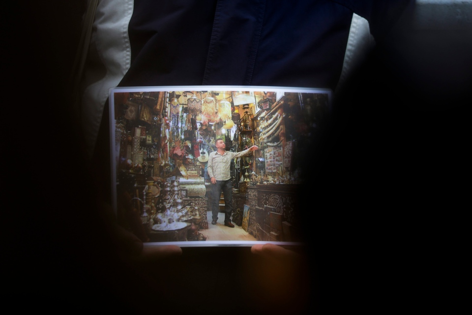 In this photo taken Sunday, Oct. 9, 2016 refugee Firas Zakri from Syria, a tour guide of the so-called 'Refugee Tours' shows a photograph of the market at his hometown Aleppo as he tours with a group of people through the district of Neukoelln in Berlin. (AP Photo/Markus Schreiber)
