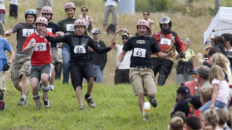 Competitors race downhill after a wheel of cheese during the 2nd Annual Cheese Rolling Festival on Blackcomb mountain in Whistler, B.C. Aug. 15, 2009. (THE CANADIAN PRESS/Jonathan Hayward)