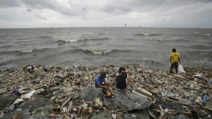 Filipinos scavenges for recyclable materials from the trash that was washed ashore by strong waves brought about by Typhoon Haima in Manila, Philippines on Thursday, Oct. 20, 2016. (AP / Aaron Favila)