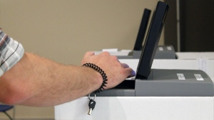 A ballot is inserted into an electronic voting system. (KARYN MULCAHY)