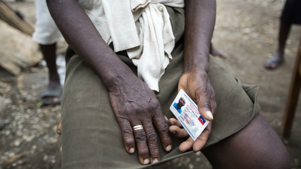Bertha Mesilier holds the national identification card of her missing husband Edma Desravine, who was last seen seeking refuge from the heavy rainfall and winds brought by Hurricane Matthew, in Port-a-Piment, a district of Les Cayes, Haiti on Tuesday, Oct. 18, 2016. (AP / Dieu Nalio Chery)
