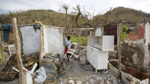 Mona Habraham salvages a chair from her home, destroyed by Hurricane Matthew in Port-a-Piment, a district of Les Cayes, Haiti on Wednesday, Oct. 19, 2016. (AP / Dieu Nalio Chery)