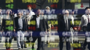 People are reflected on the electronic board of a securities firm in Tokyo, Friday, Oct. 21, 2016. (AP / Koji Sasahara)