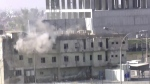 In this image made from video, smoke rises from a building where two militants are believed to be holed up, according to Rudaw TV, in Kirkuk, Iraq on Friday, Oct. 21, 2016. (Rudaw TV)