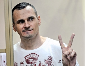 In this Tuesday, Aug. 25, 2015 file photo, Oleg Sentsov gestures as the verdict is delivered, as he stands behind bars at a court in Rostov-on-Don, Russia. (AP Photo, file)