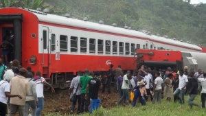 In this image made from video, people walk beside a derailed train carriage after an accident in Eseka, Cameroon on Friday, Oct. 21, 2016. (Equinox TV)