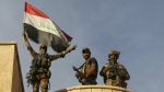 Iraq's elite counterterrorism force soldiers raise an Iraqi flag over the main church in Bartella, Iraq on Friday, Oct. 21, 2016. (AP / Khalid Mohammed)