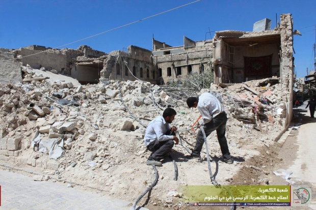 In this file photo taken Aug. 20, 2016 and provided by the local council of Aleppo city, Syrians workers fix electricity cables after airstrikes, in Aleppo, Syria. (Local Council of Aleppo City via AP)