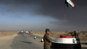 Iraqi troops guards a checkpoint near the village of Awsaja, Iraq, as smoke from fires lit by Islamic State militants at oil wells and a sulfur plant fills the air on Saturday, Oct. 22, 2016. (AP / Adam Schreck)