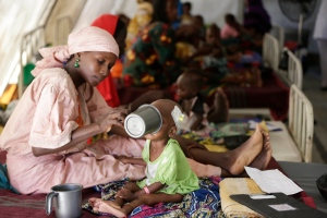 In this Monday Aug. 29, 2016 file photo, a mother feeds her malnourished child at a feeding centre run by Doctors Without Borders in Maiduguri Nigeria. During its seven-year uprising, Boko Haram extremists have killed more than 20,000 people and displaced more than 2.6 million in Nigeria and neighboring Cameroon, Niger and Chad. ( AP Photo/Sunday Alamba, File)