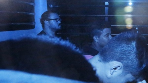 In this photo taken through a tinted glass, Rurik Jutting, left, a British banker, sitting in a prison bus, leaves a court in Hong Kong Thursday, April 2, 2015. (AP / Kin Cheung)