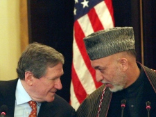 Afghan President Hamid Karzai whispers to U.S. Special Representative to Pakistan and Afghanistan Richard Holbrooke ahead of a news event in Kabul, Afghanistan, on Sunday, Feb. 15, 2009. (AP / Musadeq Sadeq)