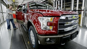 In this March 13, 2015, file photo, a worker inspects a new 2015 aluminum-alloy body Ford F-150 truck at the company's Kansas City Assembly Plant in Claycomo, Mo. (AP / Charlie Riedel, File)