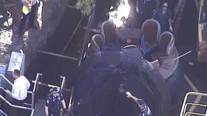 In this image made from video, rescue personnel stand by the Thunder River Rapids ride at Dreamworld on the Gold Coast, Australia, Tuesday, Oct. 25, 2016. (Channel 9 via AP)