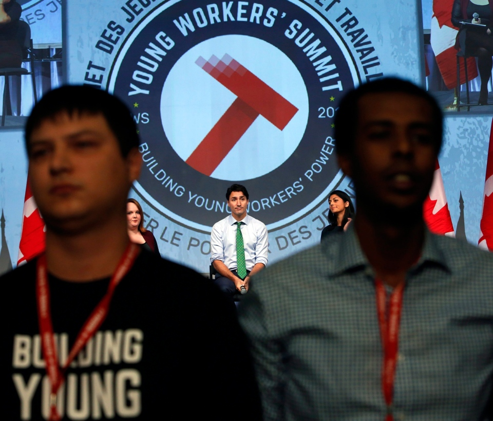 Protesters turn their backs on Prime Minister Justin Trudeau as he addresses the Canadian Labour Congress National Young Workers' Summit in Ottawa on Tuesday October 25, 2016. (THE CANADIAN PRESS/Fred Chartrand)
