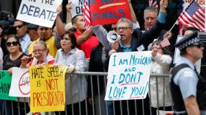 In this June 29, 2015, file photo, protesters gather across the street from a restaurant in Chicago before Republican presidential candidate Donald Trump spoke to members of the City Club of Chicago. (AP / Charles Rex Arbogast, File)