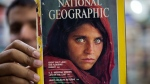Pakistan's Inam Khan, owner of a book shop shows a copy of a magazine with the photograph of Afghan refugee woman Sharbat Gulla, on Oct. 26, 2016. (AP / B.K. Bangash)