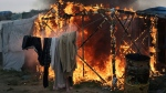 "A tent burns in the makeshift migrant camp known as ""the jungle"" near Calais, northern France, Wednesday, Oct. 26, 2016. Firefighters have doused several dozen fires set by migrants as they left the makeshift camp where they have been living near the northern French city of Calais. (AP Photo/Thibault Camus)"