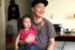 In this March 19, 2015, file photo, Korean adoptee Adam Crapser poses with daughter, Christal, 1, in the family's living room in Vancouver, Wash. (AP / Gosia Wozniacka)