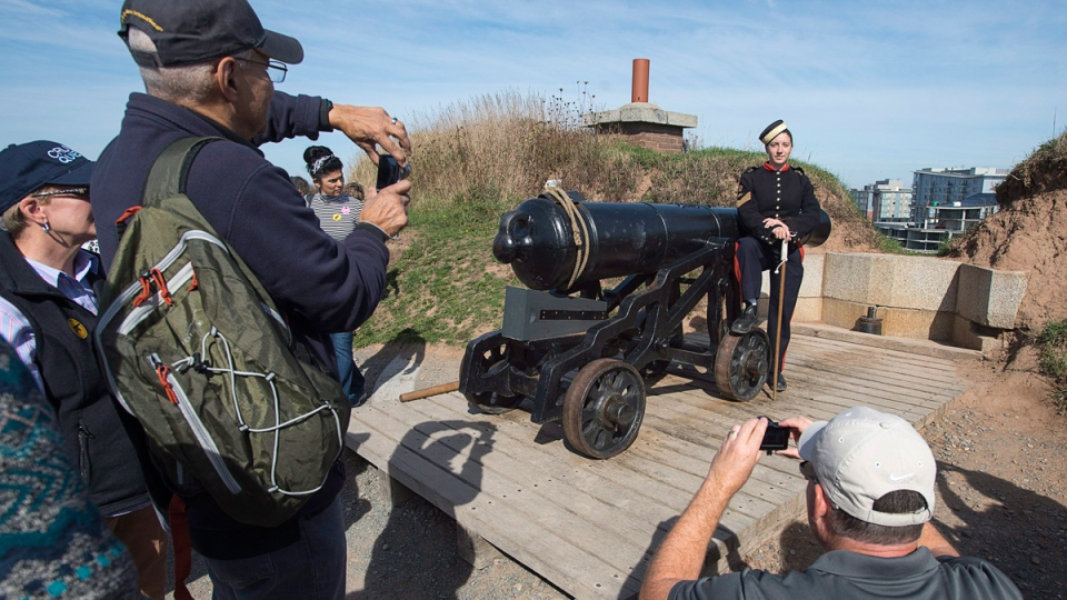 Sgt. Brittany Avery, dressed as the 3rd Brigade Royal Artillery of 1869, poses for tourists after firing the noon gun at the Halifax Citadel National Historic Site on Oct. 7, 2016. (Andrew Vaughan / THE CANADIAN PRESS)