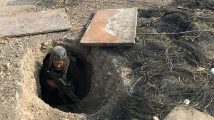 A soldier with Iraq's elite counterterrorism force inspects a tunnel made by Islamic State militants in Bartella, Iraq, on Oct. 27, 2016. (Ali Abdul Hassan / AP)
