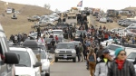 An exodus of Dakota Access Pipeline protesters move south on Highway 1806 as a line of law enforcement slowly push the protest effort from the Front Line Camp to the Oceti Wakoni overflow camp a few miles down the road in Morton County, N.D., Thursday, Oct. 27, 2016. (Mike McCleary / The Bismarck Tribune)