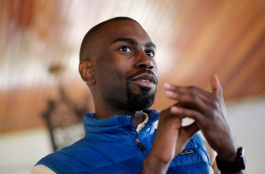 In this March 26, 2016, file photo, Black Lives Matter activist DeRay Mckesson, who was seeking the Democratic nomination to run for mayor of Baltimore, chats with campaign volunteers in Baltimore. (AP Photo/Patrick Semansky, File)