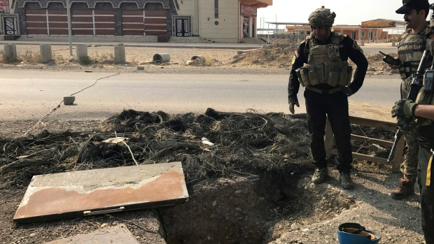 A soldier with Iraq's elite counterterrorism force inspects a tunnel made by Islamic State militants in Bartella, Iraq, Thursday, Oct. 27, 2016. (Ali Abdul Hassan/AP)