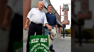 "Billy Goat Tavern owners Sam Sianis, left, and his son Bill pose with ""Billy"" the goat outside their tavern on Madison Street in Chicago on Oct. 20, 2015. (Paul Beaty/AP)"