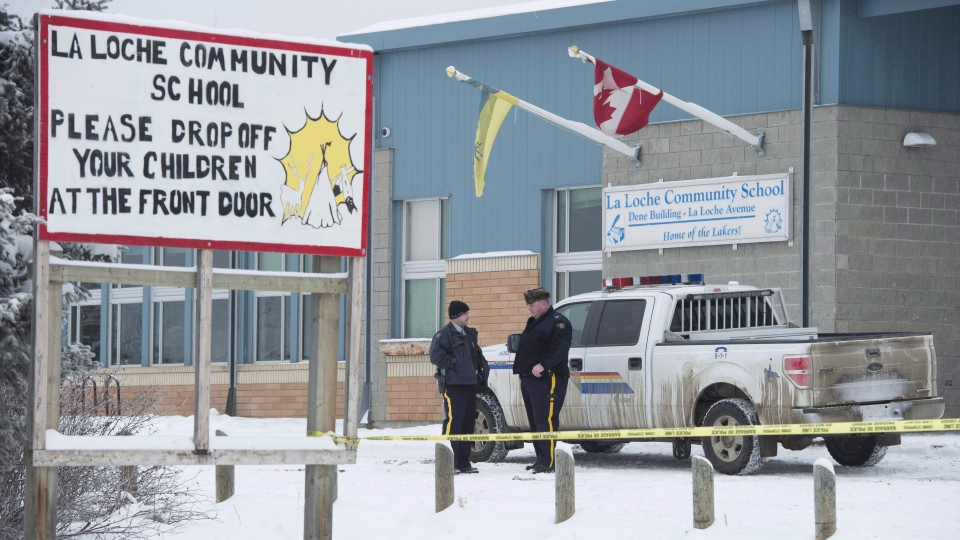Members of the RCMP stand outside the La Loche Community School in La Loche, Sask., on Jan. 25, 2016. (Jonathan Hayward / THE CANADIAN PRESS)