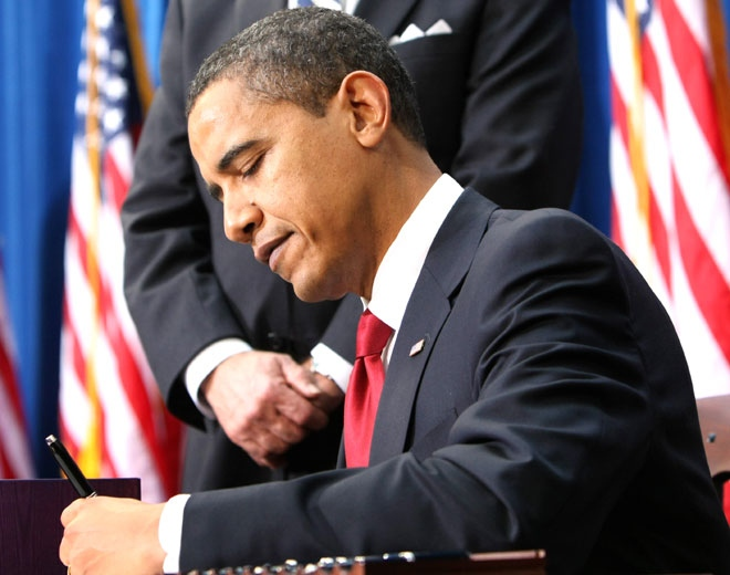 President Barack Obama signs the American Recovery and Reinvestment Act, at the Denver Museum of Nature and Science in Denver on Tuesday, Feb. 17, 2009. (AP / Gerald Herbert)
