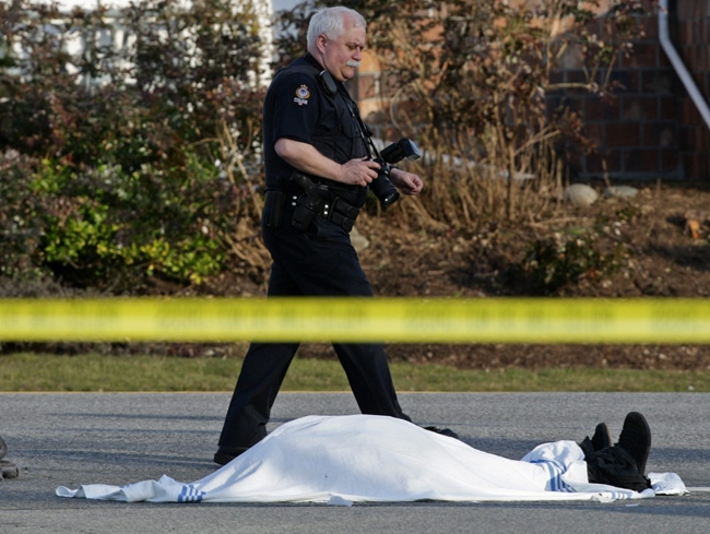 A police officer walks past a body covered by a blanket following a suspected shooting in Vancouver, B.C., on Tuesday February 17, 2009. (THE CANADIAN PRESS/Darryl Dyck)