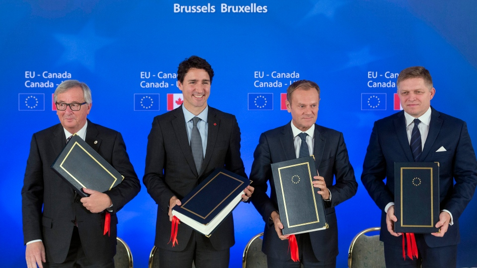 Canadian Prime Minister Justin Trudeau, second left, stands with, from left, European Commission President Jean-Claude Juncker, European Council President Donald Tusk and Slovakian Prime Minister Robert Fico after signing the Comprehensive Economic and Trade Agreement  in Brussels, Sunday, Oct. 30, 2016. (AP Photo/Thierry Monasse, Pool)