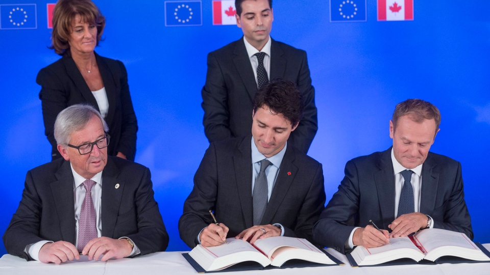Canadian Prime Minister Justin Trudeau, front center, signs the Comprehensive Economic and Trade Agreement (CETA) with European Commission President Jean-Claude Juncker, left, and European Council President Donald Tusk in Brussels, Sunday, Oct. 30, 2016. (AP Photo/Thierry Monasse, Pool)