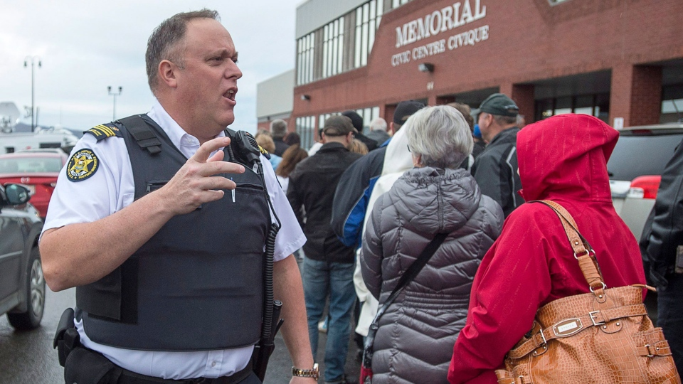 A sheriff addresses the crowd as jury selection for the trial of Jean-Claude Savoie begins in Campbelltown, N.B., on Monday, Oct. 31, 2016. Savoie is charged with criminal negligence causing death after two young brothers, Connor and Noah Barthe, were asphyxiated by an African rock python in August 2013. (THE CANADIAN PRESS/Andrew Vaughan)