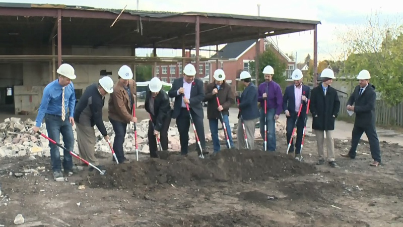 Dignitaries push shovels into the ground to officially kick off construction of the One Hundred condo project.
