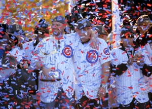 Chicago Cubs John Lester, left, holds the Commissioner's Trophy while he and Anthony Rizzo celebrate during a rally in Grant Park honoring the World Series baseball champions on Friday, Nov. 4, 2016, in Chicago. (AP Photo/Charles Rex Arbogast)