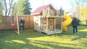 Alexander Sawatzky plays on his new play structure with his family. (CTV Winnipeg)