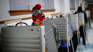 Sam Dugg fills out his ballot in a voting booth at the Nativity School in Cincinnati on Election Day, Tuesday, Nov. 8, 2016. (AP / John Minchillo)