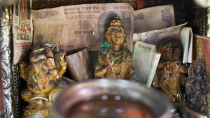 An altar with idols of Indian gods has Rupee notes as offering at a money-exchange counter in Dharmsala, India, Wed., Nov. 9, 2016. (AP / Ashwini Bhatia)