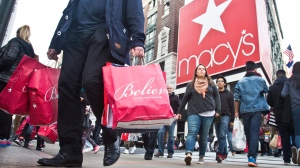 In this Friday, Nov. 27, 2015, file photo, shoppers carry bags as they cross a pedestrian walkway near Macy's in Herald Square, in New York. (AP / Bebeto Matthews)