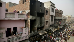 Locals crowd outside a residential building used as a garment factory, which was gutted in a fire in the outskirts of New Delhi, India on Friday, Nov. 11, 2016. (AP / Altaf Qadri)